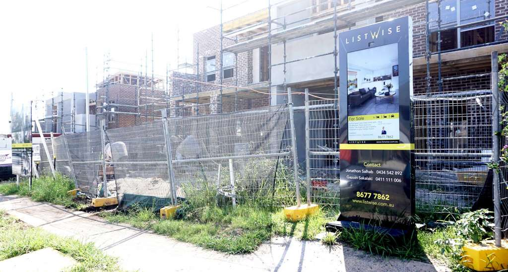 Digital sign showing image of completed development stands in front of a construction site.